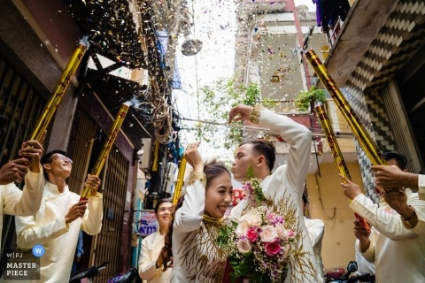 Photo of the bride and groom at the Groom House in Saigon as the groomsmen fire confetti cannons around them by a Vietnam wedding photographer.