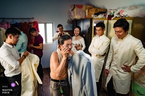 Photo of the bridal party and groom getting ready for the ceremony at the Groom House in Saigon by a Vietnam wedding photographer.