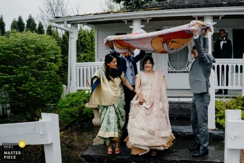 THE DOCTOR'S HOUSE wedding photography - The friends use a quilt to cover the bride in the rainning