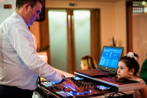 Sofia, Hotel Suite reception image of a young girl watching attentively as the DJ operates the sound board.