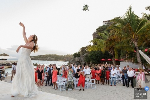 La Toubana - Guadeloupe wedding day photograph of the Launched bouquet by the bride on the beach