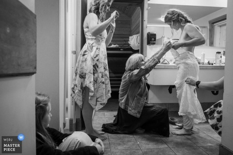 Thousand Pines Christian Camp, CA - The bride is putting her dress on in the camp bathroom with her family help.