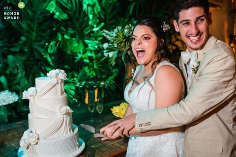 Caravelas Eventos - Botafogo | Bride and groom have  fun during the cake cutting at their reception