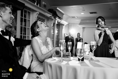 Point Lookout trouwfoto | Een bruid en bruidegom lachen tijdens een toast op een bruiloft in Maine