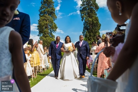 The bride is escorted down the aisle for her outdoor wedding at the Kingston Bagpuize House, London