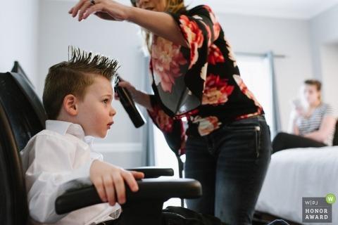 Ein kleiner Junge lässt sich in einem Hotelzimmer die Haare aufstacheln. Der Friseur beugt sich über ihn, während er auf einem Konferenzstuhl sitzt.