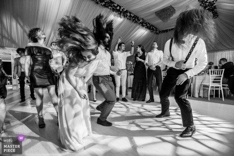 Caracal, Romania - Dolce Vita Wedding Photography of Energetic guests at the reception, banging their heads on rock music