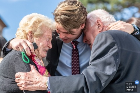 Haut-Rhin wedding photographer captured this photo of two grandparents crying tears of joy as they hand off their grandson to be wed at a ceremony at Ingersheim