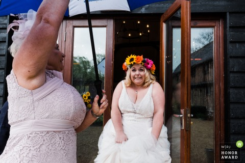 Colville Hall, Essex wedding day photography in the rain | Bride being sheltered from the rain