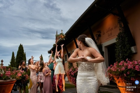 "Antica Fattoria di Paterno - Tuscany classic wedding photo of ""throwing the bouquet"""
