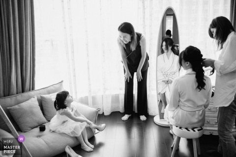 Guangzhou, China Actual Day Wedding Photography - When the bride puts on makeup, a kid tries to put on the bride's wedding shoes, which triggers the laughter of her mom and bride.