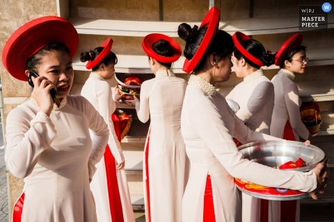 Ho Chi Minh wedding photographer captured this photo of bridesmaids in matching dresses and hats getting ready for the ceremony