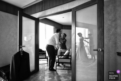 Bangkok	wedding photographer captured this black and white photo of the bride getting her dress steamed before the ceremony