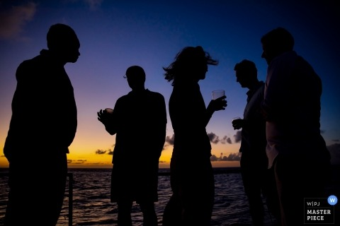 Sandals Grande St. Lucian Wedding photography showing silhouetted guests enjoying sunset cocktail hour.