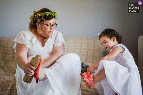 Lot-et-Garonne wedding photographer captured this photo of a bride wearing a floral crown putting on red sandals, as an identically dressed flower girl tries to do the same