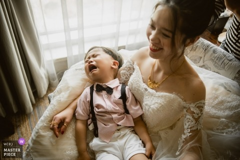 A bride holds a crying toddler in this photo captured by a Sanming wedding photographer