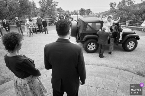 Varazze, Italy black and white wedding photo showing the bride arriving at church while groom stands waiting