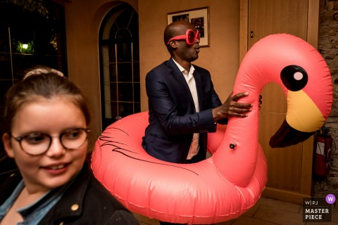 Seigneurie du Bois Benoist - wedding photo showing fun during diner with flamingo pool toy and guests
