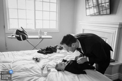 Wedding Photography at The Brandeis-Bardin Campus of American Jewish University | The groom dresses his infant nephew into a baby tuxedo, in Los Angeles