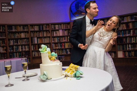 Photo of the groom and the bride enjoying the moment right after cake cutting and aggressively feeding each other at the American Jewish University-Brandeis Bardin Campus, Brandeis, CA