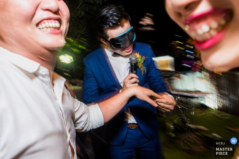 Ho Chi Minh wedding photographer captured this photo of the groom wearing a blindfold while playing a game at the reception
