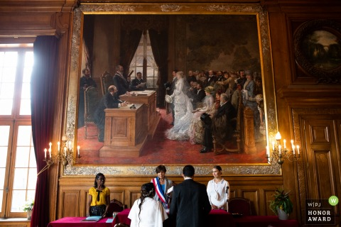 Photo of Paris wedding ceremony below giant wall painting.