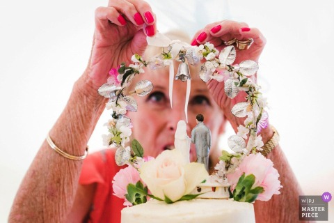 The Mill House Hotel, Berkshire, UK Weddings - Photographic Image showing Granny attaching the family cake topper to the wedding cake