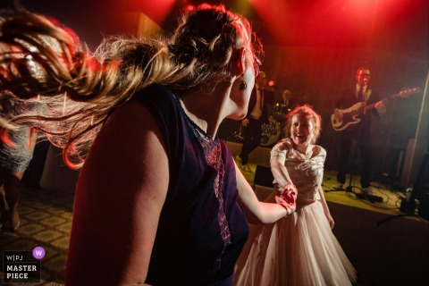This photo of the bride and bridesmaids dancing on the dance floor in front of the band was captured by an Antwerpen wedding photographer