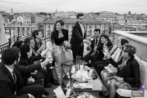 Terrazza Borromini rooftop wedding toast in this black and white photograph.