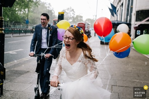 Royal Hospital Chelsea Wedding Photographer | The Bride + Groom encounter a hail storm as they scooter to the venue with balloons