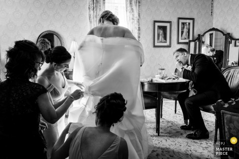 Glencairn Mansion Wedding Photographs | Image of the groom enjoying himself as the bride, her bridesmaids, and her mom try to get her bustled for the cocktail hour