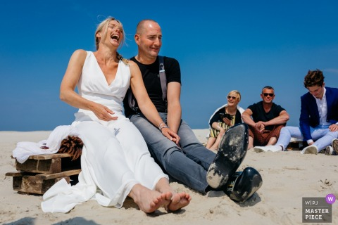 Wedding photograph of the bride and groom sitting at Terschelling during the elopement ceremony