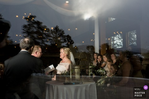 Della Terra Mountain Chateau Wedding Photographer | Picture of Indoor ceremony, looking from the outside through the large glass window.