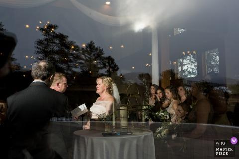 Fotograf ślubny Della Terra Mountain Chateau | Obraz ceremonii Kryty, patrząc z zewnątrz przez duże szklane okno.