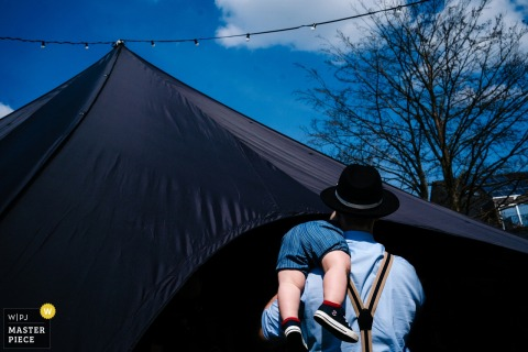 De Casteleer Photography - Image of a wedding guest as he carries his baby son on his shoulder to the tent