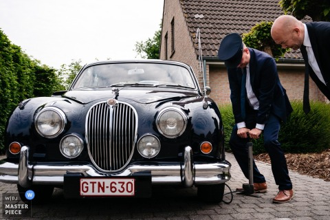 Antwerpen Wedding Photographer captured this image of the driver of the ceremonial car has a flat tire right before the couple needs to leave