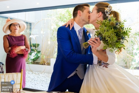 Alicante wedding photographer captured this beautiful photo of the bride and groom kissing as the mother of the groom watches nearby