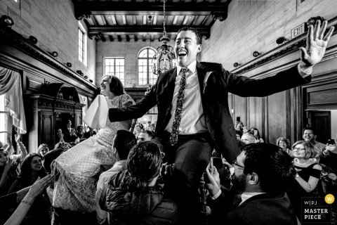 The Strathmore Mansion Wedding Photography - De bruid en bruidegom worden tijdens de hora de lucht in getild