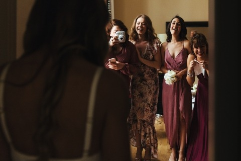 Wedding Photograph taken as bridesmaids see bride in her dress for the first time and showing their reactions
