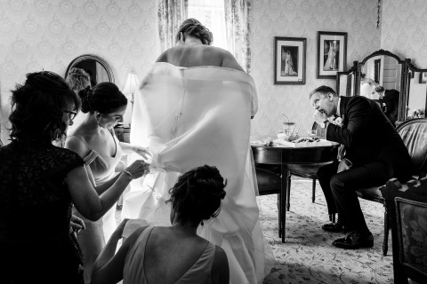 Wedding Photography of Busy Getting Ready Scene | Image of the groom enjoying himself as the bride, her bridesmaids, and her mom try to get her bustled for the cocktail hour