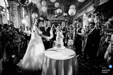 Aynhoe Park, Oxfordshire, Wielka Brytania fotografia ślubna pokazująca narzeczoną krojącą ciasto w Oranżerii w Aynhoe Park