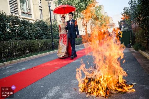 De bruid en bruidegom lopen buiten langs een rode loper door een vreugdevuur in deze bruiloftsfoto die is vastgelegd door een bekroonde Hangzhou City, China-fotograaf.