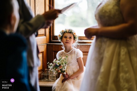 Hestercombe House Wedding Photographer - One of the flowergirls watches on as the Bride speaks to the registrar