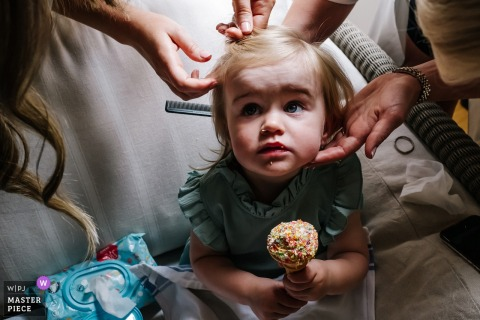 Flowergirl eats ice cream, whilst having her hair done as captured by Micklefield Hall wedding photographer.