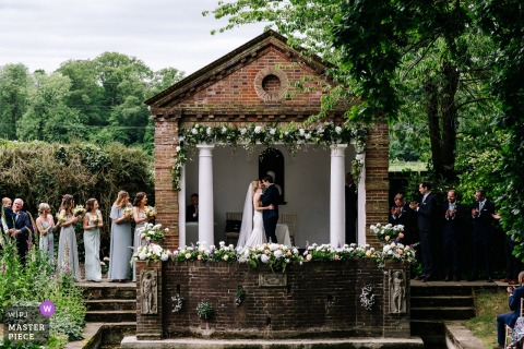 Micklefield Hall Outdoor Wedding Ceremony Photography of Bride + Groom First Kiss