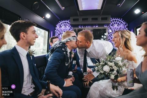 Ein Mann küsst den Bräutigam, während ihm auf diesem preisgekrönten Hochzeitsfoto, das von einem Dokumentarfotografen aus Cleveland, OH, aufgenommen wurde, die Augen verbunden sind.