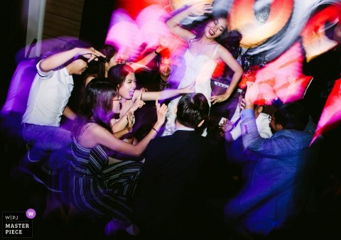 Lang Le Bau Co wedding reception photography of the bride dancing with guests.