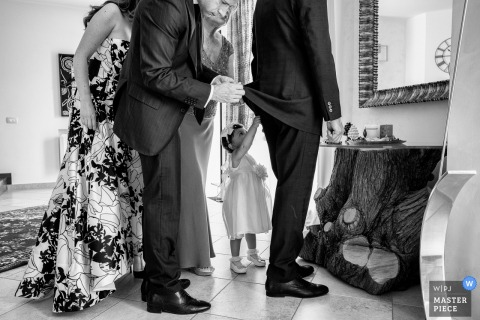A groomsmen helps another man get ready while a little girl tries to help as well in this photo captured in the Castello Xirumi di Serravalle by a Sicily wedding photographer.