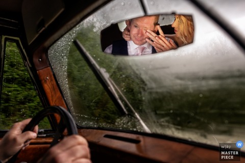 Tenuta di Papena, Tuscany image of the bride and groom reflected in the drivers mirror of the limo car