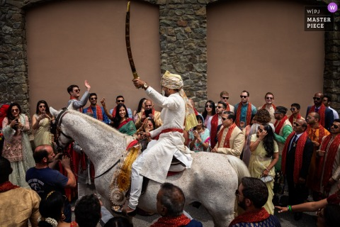 Renaissance Tuscany Il Ciocco Destination Indian wedding photograph of groom arriving on horseback with sword raised